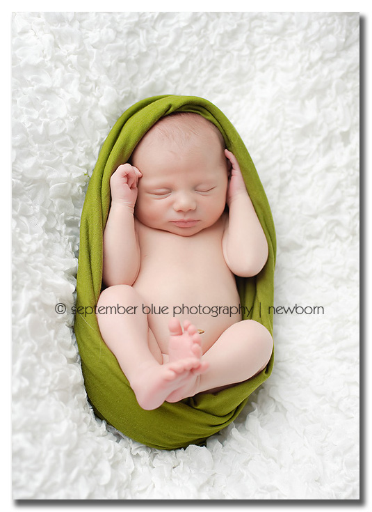 newborn wrapped in green
